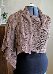 This shawl pattern is constructed in two pieces that are seamed together at the end, allowing for symmetrical leaf patterns at the edges, with a lace panel separating the two edges.