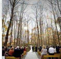 Guests sat on wooden benches under towering trees in the Woodland Chapel at Woodsgate. The clearing exuded the natural, rustic feel the couple was looking for.