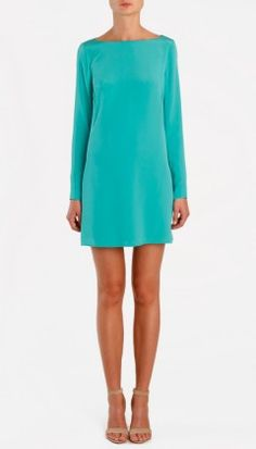 Sleek and clean shift dress with high neck line and narrow arms with hidden zippers at sleeves that add extra interest to this sophisticated take on a modern shift. Dramatic deep slit at back.