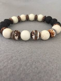 "Diffuser Bracelet: Diffuser, Essential Oil, Aromatherapy, Lava Bead / Rock Bracelet for men or women. Made with exquisite Hand Painted Tibetan Agate Gemstone. Size shown is a size medium 7 1/2"". Smaller and larger sizes available. The black Lava Rock can be scented . About Lava"