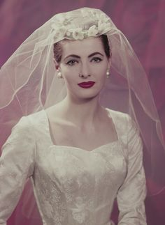 A model posing in a wedding dress and veil, June 1957