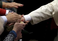 People reach out to touch the hand of Pope Francis as he places it on the head of a person during a special audience with Catholic doctors at the Paul VI hall at the Vatican November 15, 2014. REUTERS/Alessandro Bianchi