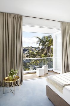 Neutral sleeping space feels like a cocoon with a whole wall of drapery. PohioAdams Architects .