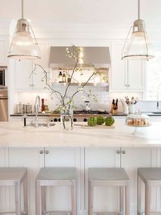 Bright kitchen. Shelf under hood. Sink in the island. Metal stools.