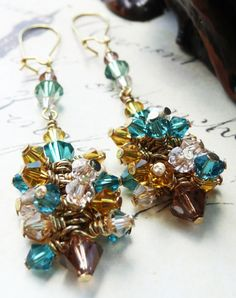 A multitude of wire wrapped crystals adorn these dangle earrings. From Capri Blue to Chocolate brown topaz, to sunflower yellow to a hint of peachy pink; these earrings got it going on! MEMBER - J Rock Jewelry