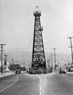 """""""Oil Island"""" was located on La Cienega Blvd., between Beverly and 3rd Street. The wooden derrick was originally constructed in 1907 in the middle of a bean field. When the city extended La Cienega to Sunset Blvd., there was a dispute over the cost of the well, so the city built around it. In 1946, an agreement was struck and the well was dismantled. (LAPL) Bizarre Los Angeles."""