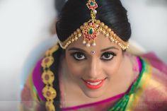 Traditional Southern Indian bride wearing bridal silk saree, jewellery and hairstyle. Temple jewelry. Jhumkis. Maang Tikka. Silk kanchipuram sari. Braid with fresh flowers. Tamil bride. Telugu bride. Kannada bride. Hindu bride. Malayalee bride. Indian Bridal Makeup. Indian Bridal Fashion.