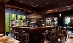 foorni.pl | Restauracja Cachitos – styl eklektyczny, drewniane stołki barowe, ściana z szarej cegły, zielone oświetlenie ściany