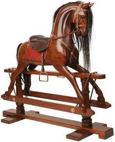Reproduction Victorian Rocking Horse ~ hand carved & polished from solid mahogany. Saddles and bridle are made of leather and the hardware is brass.
