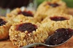 """A seasonal favorite, buttery balls of dough are rolled in toasted nuts and filled with jam. These little gems get their name from the fact you use your """"thumb"""" to make an indentation into each ball of dough for the jam. From Joyofbaking.com With Demo Video"""
