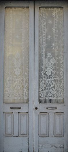 Sometimes these lace curtains can look a little outdated, but with these white-washed antique wooden doors they look gorgeous.. via TRACCIAMENTI on Flickr.