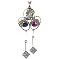 An elegant openwork 14K gold and silver pendant is set with a cushion-cut sapphire (7.35 x 6 x 4 mm, approximately 1.55 ct), a pink tourmaline (7.3 x 6.7 x 4.4 mm, approximately 1.35 ct), and old mine and rose cut diamonds (estimated total diamond weight 1.80 ct).  Length with bail 79 mm (3 in.)  Width 33 mm (1 1/4 in.) Circa 1900.