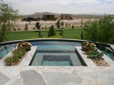 Linear planters adjacent to the raised spa direct one's eye to the curved pool edge and panoramic golf course view.