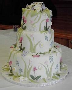 This cake is covered in rolled fondant. Each flower and leaf is colored, cut and placed individually. Very labor intense,