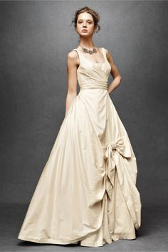 Sweeping Taffeta Ball Gown, Vintage Cream. Crisp matte taffeta curves this way and that beneath a dramatically scooped neckline, before unfurling into a bow- topped A-line skirt. (Don't forget to slip a hanky and a good luck charm into the hidden side pockets.) A Hitherto original, made exclusively for BHLDN.