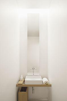 Minimalist powder room. With large metal basket of toilet paper underneath