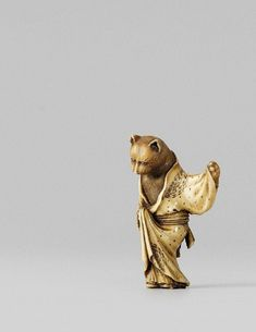 """A Tokyo school ivory netsuke of a cat. Late 19th century.  Standing upright and clad in a loosely tied kosode open at the chest and coquettishly lifting the garment in front. The ivory stained for effect. Inscribed Masaka. Late 19th century.""""Cats are said to be able to turn into young women. The best-known legend is """"Nabeshima no neko"""" (The Cat of Nabeshima), and maybe the cat here represents O Toyo, the lover of a Nabeshima daimyô in Hizen province."""