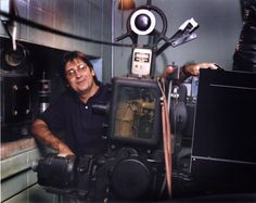 Tom Magocs standing next to old 35 mm projector.