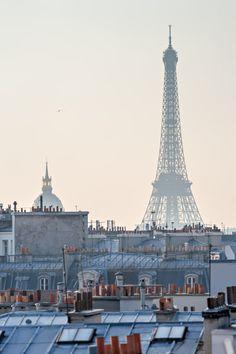 La Tour Eiffel et les Invalides en ombre chinoise derrière les toits de Paris.