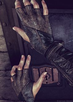 Her stiff fingers covered partly in her intricate worn-in leather gloves worked at the rusted lock on the door, feeling the cold metal against  her skin. It wasn't a particularly nice feeling, but it did feel a little good against the skin that she had worked so hard it had gone raw.