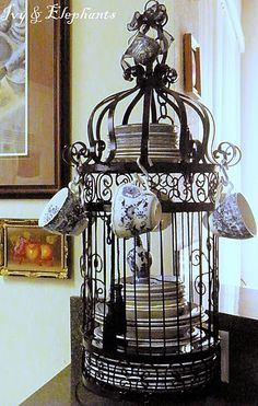 Display of dishes in birdcage...this would be so pretty for Christmas dishes in that I have a beautiful set that also has small coffee cups with very delicate handles ... Don't use them (well, I put flowers in them) they would be pretty hanging on the side of this.  CB