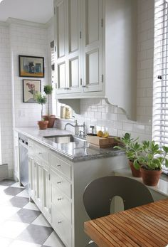 Nice kitchen details. Love the white subway tiles on the walls plus the gray and white diamond-patterned floor. Nice cutout sides on the hanging cupboard.