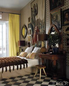 Spanish Conquest: The master bedroom includes a tapestry by Rubens, a 17th-century octagonal mirror, and a 19th-century neo-Gothic dressing table; the wallpaper was designed by Castillo.