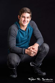 This senior looks great as he squats down on our black backdrop in our Frisco studio.