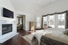 Bedroom featuring high ceiling, marble hearth with TV mounted above, dark hardwood flooring and white all around.