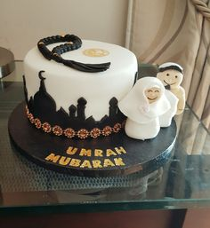 Umrah mubarak cake with edible fondant characters .