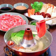 Shabu Shabu...placing beef and vegetables in hot water then dipping it in