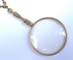 "Vintage Magnifying Glass and Victorian Button by FawneyFortune: This magnifying glass is a lovely example of detailed vintage finery. It hangs from a 28"" antiqued brass chain with matching lobster clasp, and includes vintage links and an authentic Victorian metal button. The button itself is predominantly silver-toned with art nouveau gold-toned flowers and detail in the center, and contrast details along the edge. The delicate design of this piece hearkens to a more romantic, gentile time."