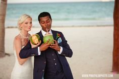 Bride and groom sipping on coconut filled cocktails during cocktail hour at this fun filled beach wedding. #mishkadesignsmexico #secretsmaroma