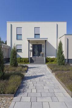 Der gerade angelegte Weg führt über Stufen zur Haustür. Die Pflanzbeete aus Metall entsprechen dem klaren Design, dass einladend wirkt. #rinnbeton #design #gartengestaltung