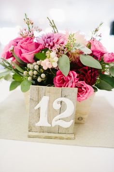 This is very in line with our theme - the rustic wood table numbers and the beautiful flowers!!  Just would prefer more of the brighter pink colours, but otherwise it's amazing!