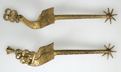 Pair of Rowel Spurs Date: 15th century Culture: French Medium: Copper, gold Dimensions: 14.25.1705a: H. 9 13/16 in. (25 cm); W. 3 1/4 in. (8.3 cm); D. 1 11/16 in. (4.3 cm); 14.25.1705b: H. 9 13/16 in. (25 cm); W. 3 3/8 in. (8.6 cm); D. 1 11/16 in. (4.3 cm)