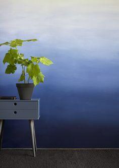 Verdeel je muur denkbeeldig in 3 tot 4 (ongelijke) horizontale banen. Meng een deel van je verfkleur in 2 tot 3 tinten naar wit. Zorg dat je in 1 keer voldoende mengt voor je muur. Breng met een roller aan de onderzijde van de de muur een baan aan in de volle kleur. Verfde banen opzettelijk grof en ongelijk om een natuurlijk verloop te creëren. Na het aanbrengen van de tweede tint, breng je met behulp van een plantenspuit en een kwast (of spons) een vloeiend verloop aan tussen de 2…