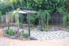 Dog proof backyard in California water-wise-small-backyard-with-flagstone-patio-pergola-and-drought-tolerant-plants-small-california-backyard-with-big-dogs.jpg