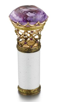 A Fabergé Amethyst, Gold and Enamel Parasol Handle, Moscow, circa 1900. The large cushion-shaped faceted amethyst handle supported on an openwork mesh basket in gold, the intersections set with rubies, the collar within two-colour gold laurel bands and enamelled translucent oyster over a wavy guilloché ground, marked with Cyrillic initials KF and with 56 standard.