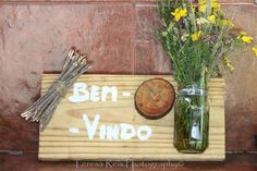 Placa de Bem-Vindo com frasco de flores campestres, rodela de tronco de pinheiro e molhinho de  ramos de pinheiro