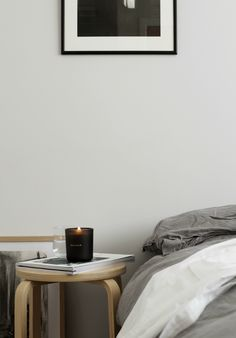 Minimal grey bedroom. Scented candle balsam with wooden wick and a beautiful smell.