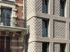 Designed by Avenier Cornejo Architectes, the building limits consumption thanks to a south-west oriented facade, aluminum shutters and solar panels. Historical Architecture, Residential Architecture, Glazed Brick, Solid Brick, Brick Construction, Sliding Wall, Brick And Stone, Stone Work, Brick Facade