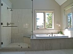 Built in tub next to shower with knee high wall in between. Glass all around to ceiling.