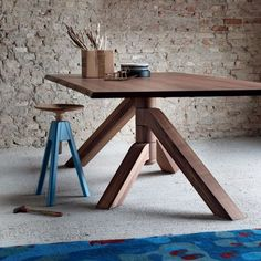 a highly adaptable table  featuring four legs that rotate around the central base of the table