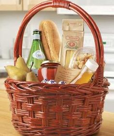 Gift basket containing pears, pasta, sauce, bread, sparkling water, chocolates and olive oil