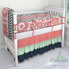 Crib bedding in Coral Scribbles, Solid Mint, Solid Navy, Solid White Minky, Coral Zig Zag, Coral Suzani, Solid Icey Mint, Solid Coral, White and Navy Zig Zag. Created using the Nursery Designer® by Carousel Designs where you mix and match from hundreds of fabrics to create your own unique baby bedding. #carouseldesigns