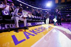 Los Angeles Lakers' Kobe Bryant sits on the bench, he is the last player to be introduced to the crowd, as head coach Mike D'Antoni, right, looks on before the NBA basketball game against the Toronto Raptors in Los Angeles, Sunday, Dec. 8, 2013. It was Bryant's first game back after a torn left Achilles tendon injury on April 12th. (AP Photo/Danny Moloshok)
