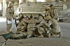 U.S. Marines pray over a fallen comrade at a first aid point after he died from wounds suffered in fighting in Fallujah, Iraq, Thursday, April 8, 2004. Hundreds of U.S. Marines have been fighting insurgents in several neighborhoods in the western Iraqi city of Fallujah in order to regain control of the city. (AP Photo/Murad Sezer