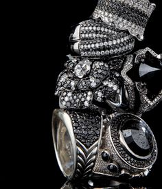 Black Diamonds ; <3 Azature ;CLOCKWISE FROM TOP: Black and white diamond scalloped ring, Aaron Basha ($12,000). Neiman Marcus, Copley Place; neimanmarcus.com. Zar ring, Azature ($75,000). azature.com. Black diamond Trinity ring, Coomi ($29,000). Neiman Marcus, SEE ABOVE. Albion ring, David Yurman ($1,900). Copley Place; davidyurman.com. Camelia Nervure ring, Chanel ($90,000). Special order, 5 Newbury St.; chanel.com. Black rhodium and black and white diamond ring, Euro Design Jewelry…