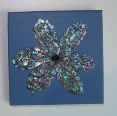 Paua Flower Picture.  Made of painted canvas with black seed beads as the centre of the flower with rows of small paua pices, time consuming but effective piece as the paua has many colours through it.
